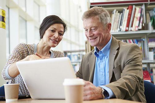 Photo of older man working at laptop with younger woman