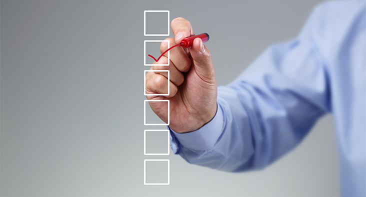 Image of person checking boxes with a red marker.