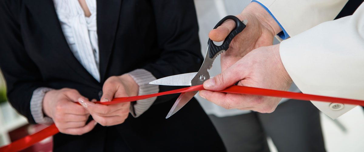 Image of business people cutting tape at an opening