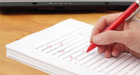 Person editing document with red ink