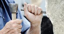 Sculptor's hands working with tools on stone block