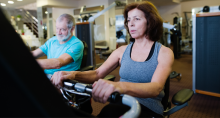 Older couple riding indoor cardio bikes