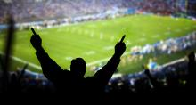 Silhouette of football fan cheering at packed stadium