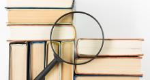 Magnifying glass on stack of books