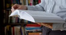 Photo of man holding large textbook