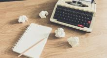 Image of typewriter and notepad on wooden desk
