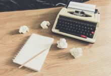 Image of typewriter and paper on wooden desk