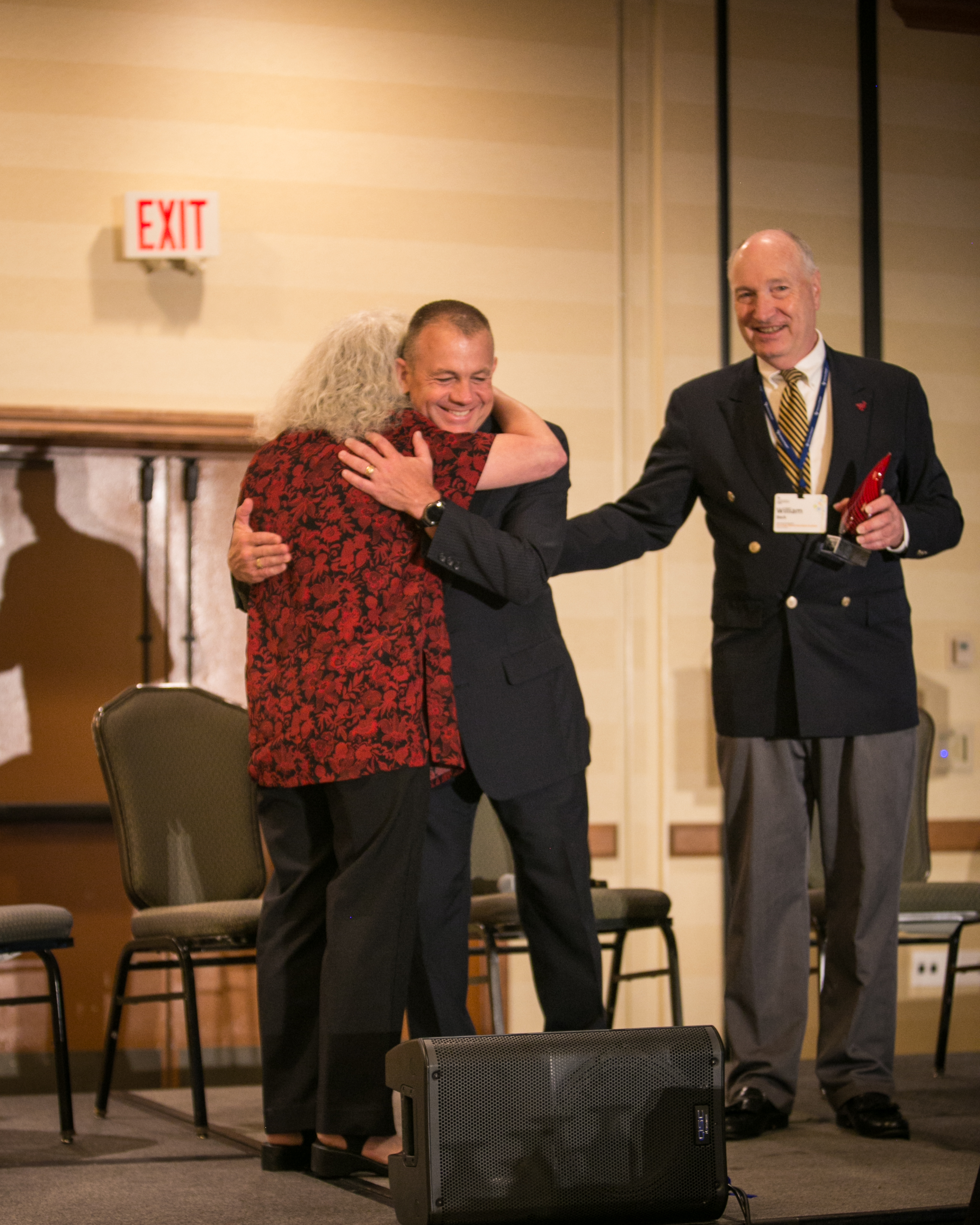 Dissertation of the Year Award Winner Dr. Roberts hugs his chair Dr. Kovacich on stage at 2017 KWB Symposium